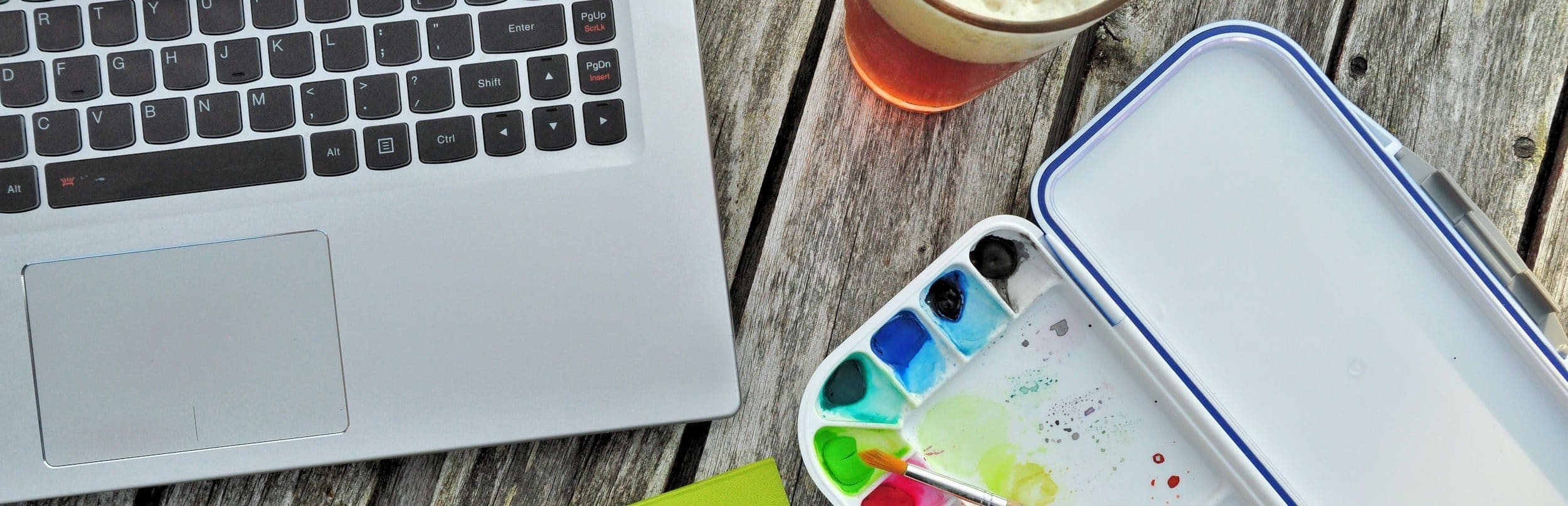 wooden table with glass of beer, green notebook, laptop computer, and watercolor paint set